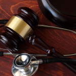 Gavel and stethoscope on a wooden surface