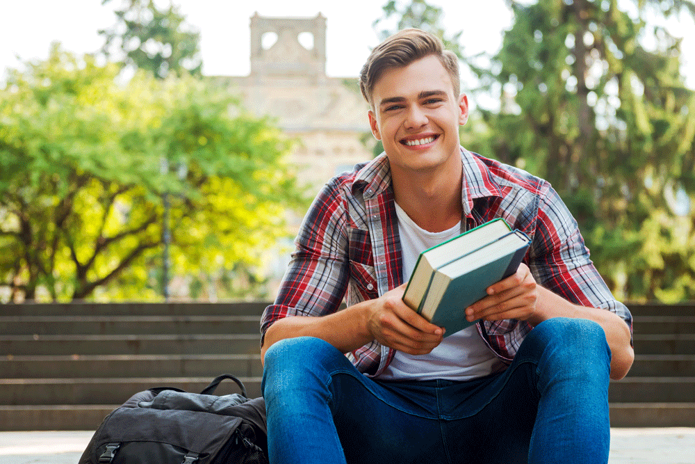 Male student sitting on university steps holding books