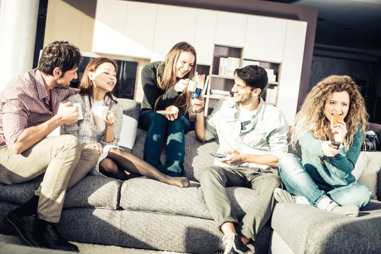 Group of students on a sofa in their house drinking coffee