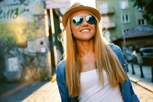 Young woman wearing sunglasses and smiling whilst walking down street