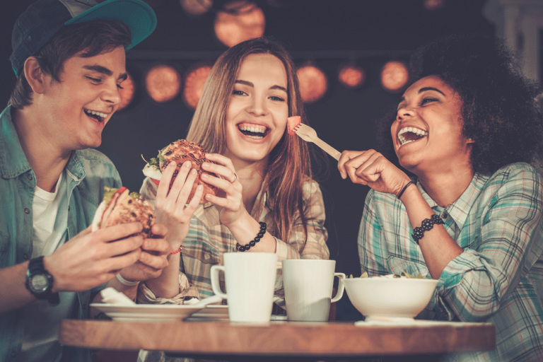 Three students laughing and eating in bar
